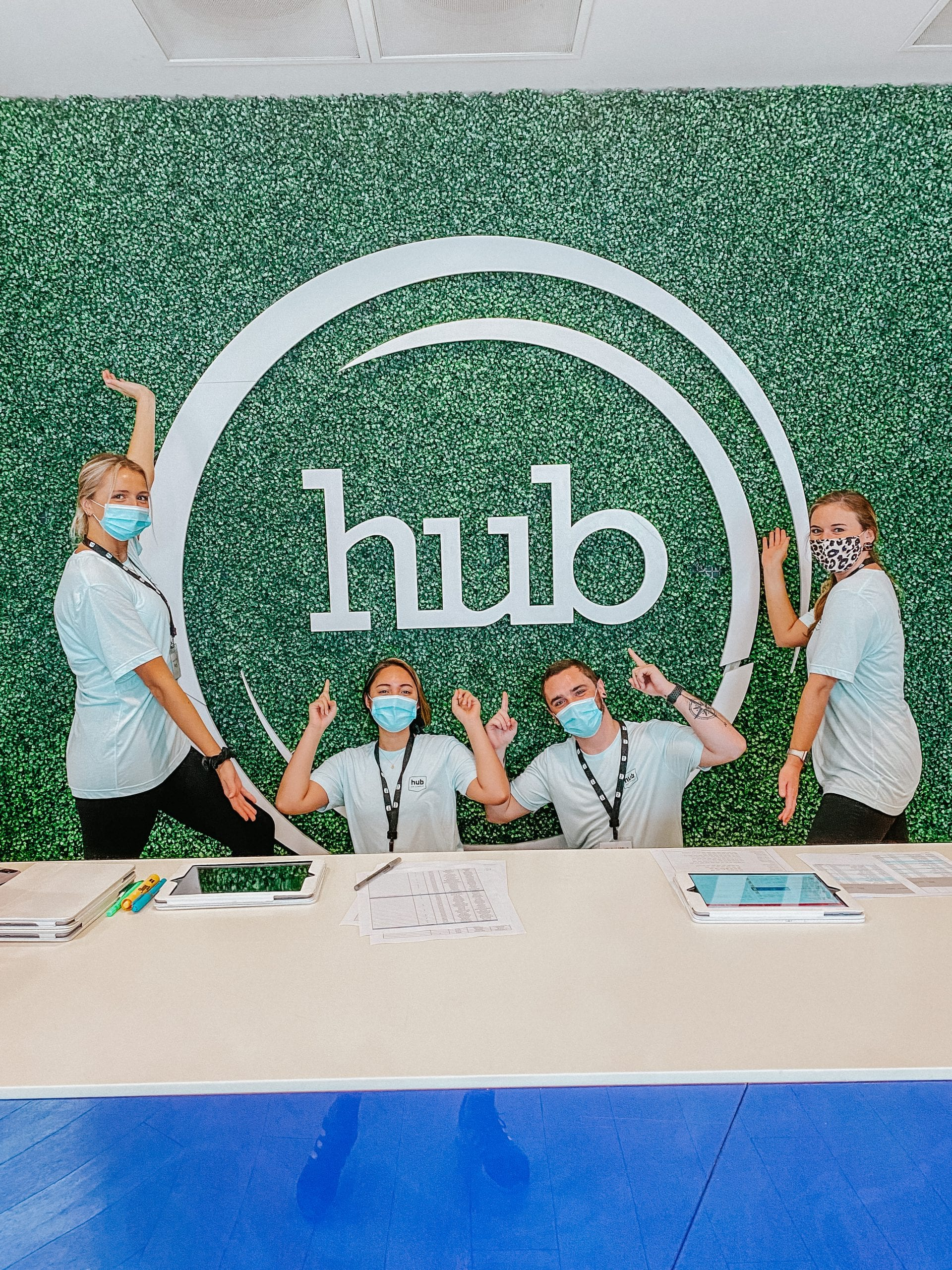 Four students posing for camera in front of Hub sign, wearing face masks